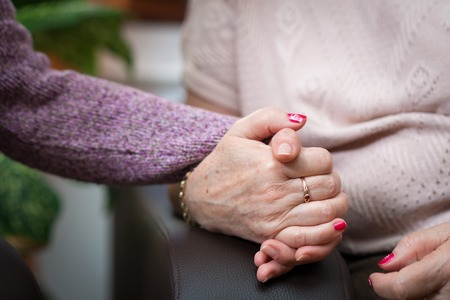 Nurse holds the senior woman hands