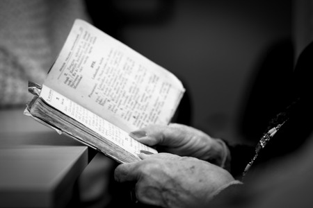 woman with hands holding Bible
