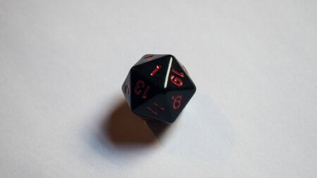 A twenty-sided dice thrown onto a white surface. Dice in black and red colors. White background. Stock Photo