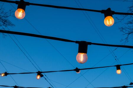 Light bulbs against the evening blue sky. Lanterns glowing with a pleasant warm yellow light.