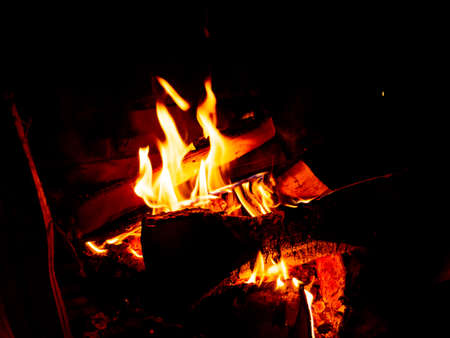 Photo a bright, saturated fire. Fire inside the fireplace, heat. Burning boards on a dark background.