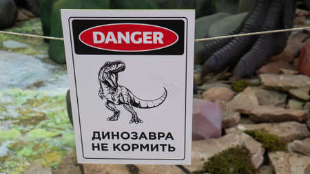 Saint-Petersburg, Russia. November 2019: A plate with a dinosaur, on which is written in Russian the danger zone , do not enter.