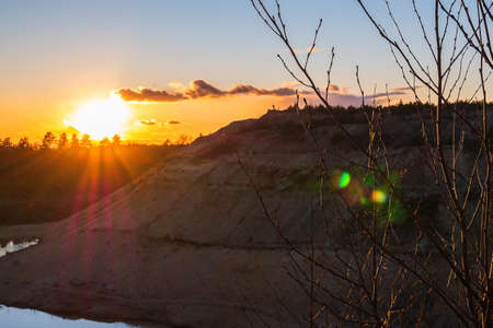 Sunset in the background of a large mountain made of sand. Sunset in the background of an abandoned quarry. Stock fotó