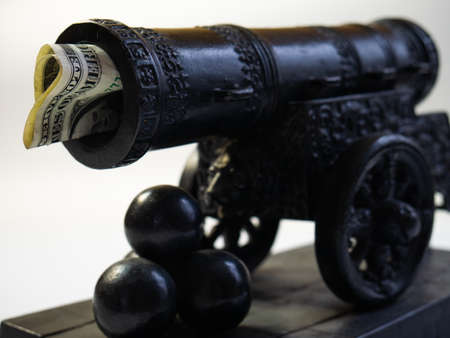 The moneys stuck in the gun. Cannon shot with money. Empty waste of money. Gun shooting kernels in miniature. 免版税图像 - 150869851