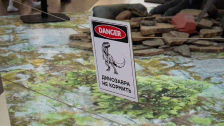 A plate with a dinosaur, on which is written in Russian the danger zone , do not enter.