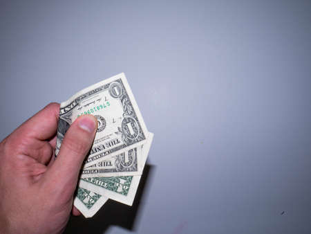 The hand holds and squeezes the dollars. Money in a fist. Its holding out dollars. First-person payment.
