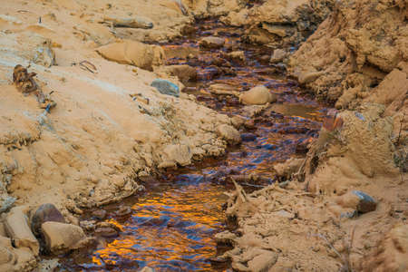 Water flow against the background of stones and sand. The flow of water in the sandy area. The appearance of water in the desert.