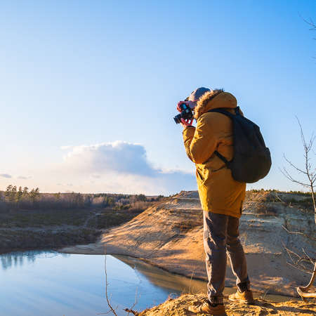 The photographer shoots a beautiful landscape, standing on the mountain. A man stands on a mountain and takes pictures of the lake.