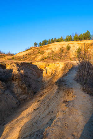 A narrow trodden path on the mountain. Dangerous transition with the ability to fall down. A sandy mountain with a road. Imagens