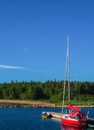 Beautiful red yacht against the blue sky and green forest. Its a great contrast. Good background for a postcard.