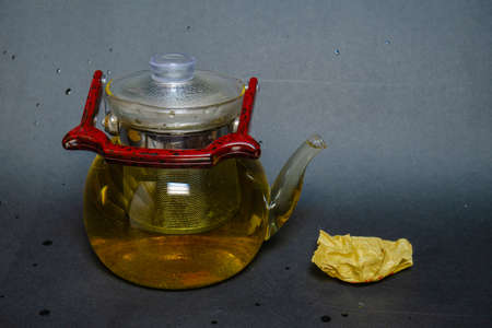 A kettle with a red handle, next to pressed green tea with mint. Tea party.