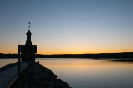 The silhouette of the church at night, the church off the coast of the sea. A small chapel in the background of the sunset. 免版税图像