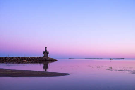 Beautiful pink sunset, a boat passing by the church. A church standing on the shore of a lake or sea. Reflection of the sunset in the water.