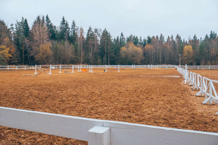 Pure white racetrack against the backdrop of a beautiful autumn forest. White fence in the background of nature.