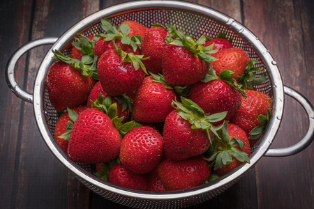 colander: Fresh strawberries in stainless steel colander on a wood surface