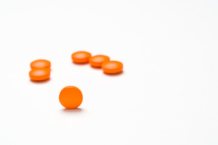 tight focus: Medication, pills spilling out onto a white surface. Tight focus on single pill. Stock Photo