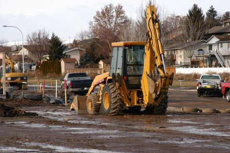 muck: yellow and black backhoe in new subdivision Stock Photo