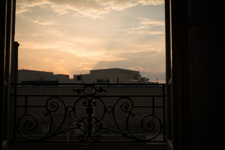 guard rail: Sunrise over Distant Bulidings through Window with Guard Rail Stock Photo