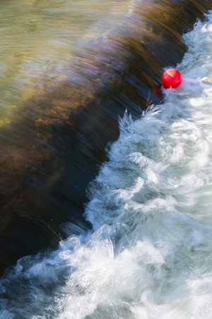 trapped: Bright Red Balloon Trapped in Flowing River