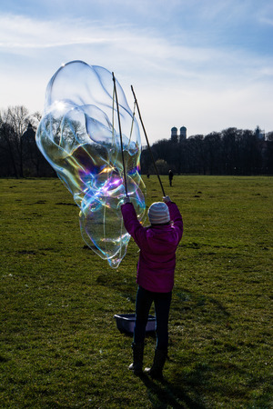 frauenkirche: Behind Shot Little Girl Blowing Bubble on Munich Germany Landscape with Frauenkirche Stock Photo