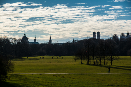 garten: Munich Cityscape under Bright Blue Cloudy Sky in Englisher Garten Stock Photo