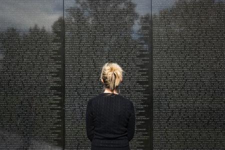 ベトナム記念ワシントン DC のランドマークの名前を見て女性の立っています。