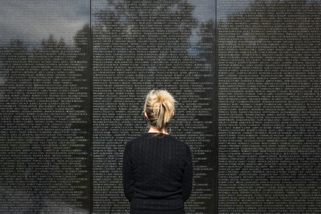 Woman Standing Looking At Names on Vietnam Memorial Washington DC Landmark Stock Photo - 71222119