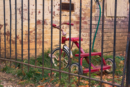 Red Children Tricycle Worn Grown Weeds House Bricks Vintage Gate Bars Toy Abandoned