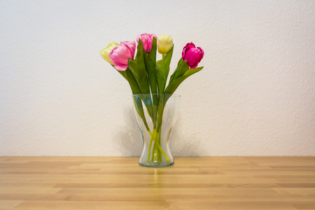 valentines day mother s: Pink Yellow Tulips Wooden Table White Wall Glass Vase