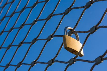 analogy: Love Lock Golden Padlock Hanging Tourist Travel Tourism Tradition Trend Strength Metal Fence Blue Sky Location Destination High Altitude Stock Photo
