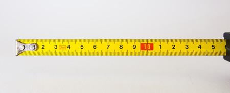 黄色の明るい線クローズ アップ建設ロールアウト テープ メジャー