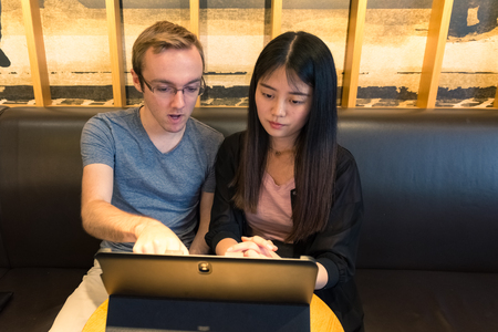 togther: European Male and Asian Girl Working Togther on Laptop Tablet Coffee Shop Casual Atmosphere Business