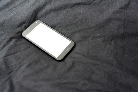 Cell Phone on Black Blanket White Screen Isolated Simple Background Fabric Banque d'images