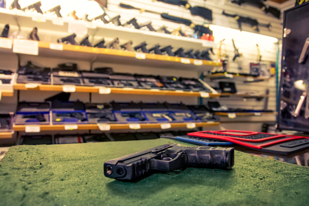 Black Combat Pistol Gun Shop Store Dealing Countertop Weapons Dangerous Sales Felt Surface Display Standard-Bild