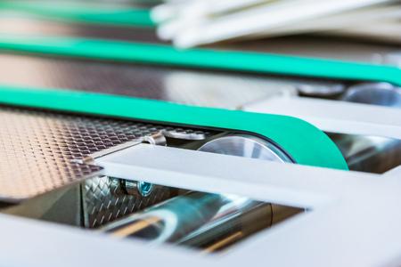 Papierfalzmaschine Förderband Gummi dünne Linien Grüne Räder Stahlbewegende Maschinerie Industrial Engineering Production Professional Standard-Bild