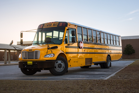 American Yellow Black School Bus on School Grounds Transportation Vehicle Banque d'images