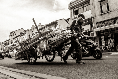 Woman Shouldering Wagon Alone Editorial