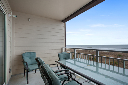 View of Beach from Apartment Balcony Empty with Table and Armchairs