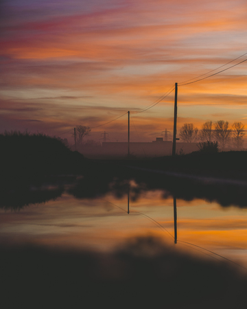 Sunset Sky Reflecting On Small Lake with Power Lines on Landscape, Afternoon Orange Purple Sky