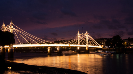 Albert bridge illuminated by lights at night with traffic