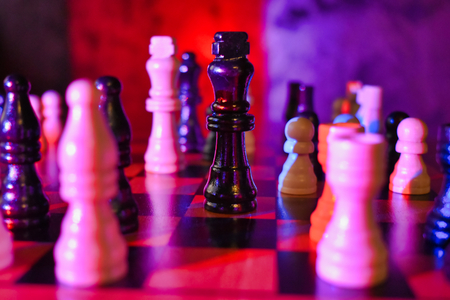 Red Blue Lit Chess Board with Focus on Black King Piece Static Shot