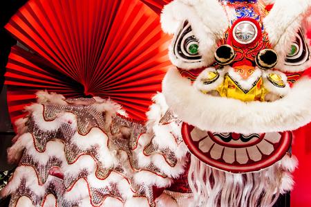 colorido león chino tradicional Año Nuevo con el ventilador rojo como fondo Foto de archivo