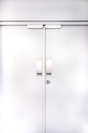 Stock Photo   Two Flush Doors With Metallic Push Sign And Door Knob