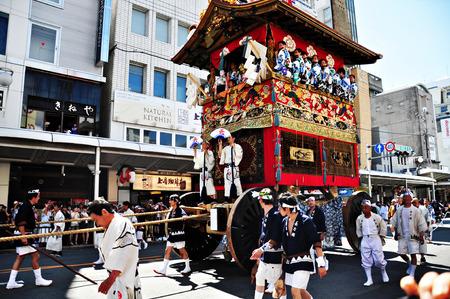 京都: 日本の伝統的衣装で、それに伴う男性と一緒に非常に装飾されたフロートがドラッグされているパレード 2011 年 7 月 17 日の京都の祇園祭の時