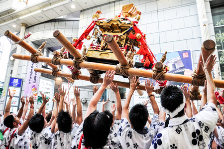 worshiped: Osaka, Japan - July 25, 2012: Golden portable shrine carried and worshiped by participants of the Tenjin Matsuri Festival, the greatest festival in Osaka boasting of a history of a thousand years.