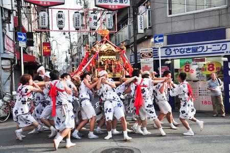 大阪、日本 - 2012 年 7 月 25 日: 黄金の御輿が行い天神祭、千年の歴史を誇る大阪の最大のお祭りの参加者によって崇拝します。