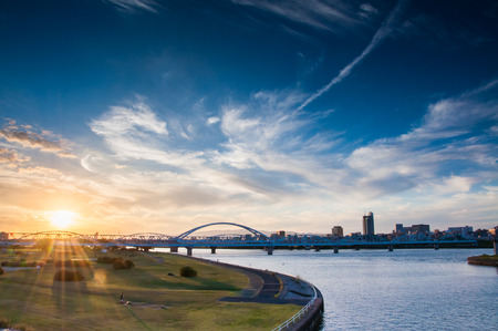 Sunset view at Yodogawa river bank with railway and buildings in the background Stock Photo