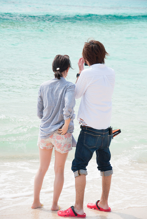 Two lovers making a selfie photo at a beautiful beach in Okinawa, Japan Stock Photo