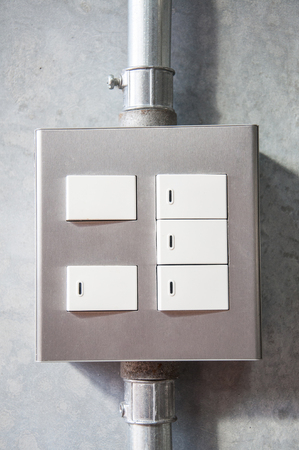 electrical light switch with pipeline on concrete background