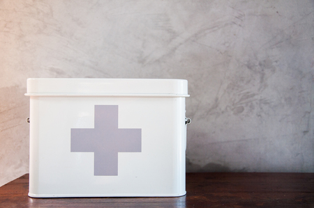 Metal first aid kit box on wooden table Imagens